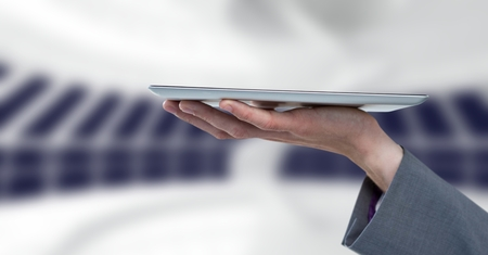 Digital composite of Hand holding tablet by windows