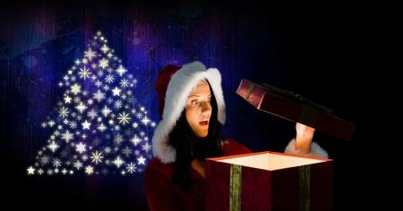 ギフトとスノーフレーク クリスマス ツリー パターン形状を開く女性サンタのデジタル合成 写真素材