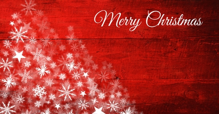 Digital composite of Merry Christmas text and Snowflake Christmas patterns on wood 写真素材