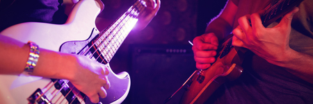 Mid section of male and female guitarist performing in nightclub Stock Photo