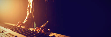 Mid section of female musician playing piano in illuminated nightclub