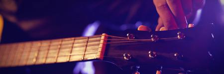 Mid section of male guitarist at illuminated nightclub Stock Photo