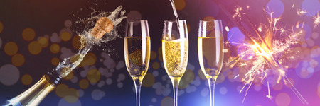 Two full glasses of champagne and one being filled against champagne cork popping Stock Photo
