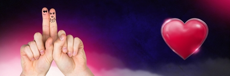 Digital composite of Valentines fingers love couple and Shiny heart  glowing with purple misty background Stock Photo