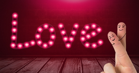 Digital composite of Valentines fingers love couple and Love text glowing neon light bulbs over wooden floor Stock Photo
