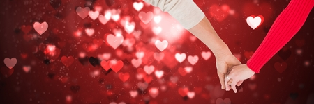 Digital composite of Valentines couple holding hands and love hearts background Фото со стока