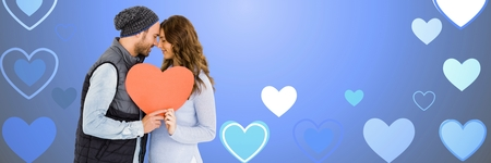 Digital composite of Valentines couple holding heart with love hearts background Stockfoto