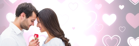 Digital composite of Valentines couple holding rose with love hearts background