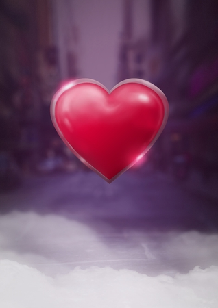 Digital composite of Shiny heart glowing with purple city misty background Stock Photo