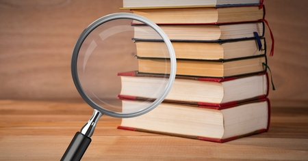 Digital composite of 3D Magnifying glass over books