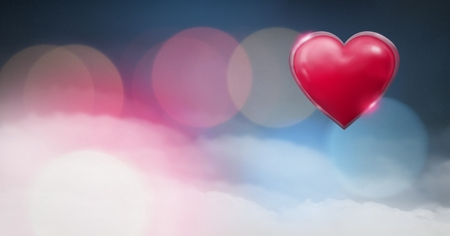 Digital composite of Shiny heart glowing with bokeh misty background Imagens