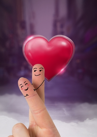 Digital composite of Valentines fingers love couple and Shiny heart glowing with purple city misty background Banco de Imagens
