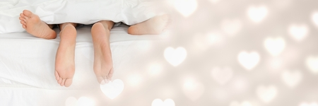 Digital composite of Couple's feet in bed with valentine's love transition hearts