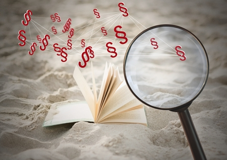 Digital composite of 3D Magnifying glass over book with section symbol icons in sand