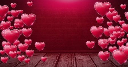 Digital composite of Shiny bubbly Valentines hearts over wooden floor Stock Photo