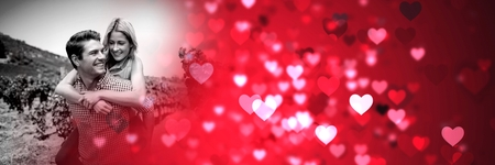 Digital composite of Couple giving piggyback with valentine's love transition hearts Stock Photo