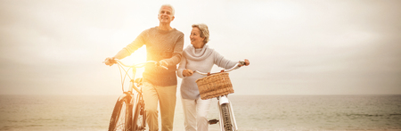Full length of senior couple with their bicycles at the beach Banque d'images
