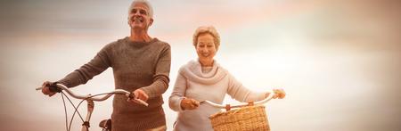 Ältere Paare , die mit ihrem Fahrrad am Strand reiten Standard-Bild