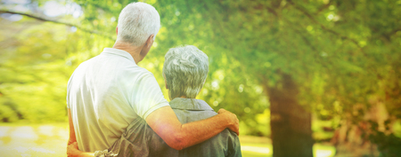 Happy old couple smiling in a park on a sunny day  Stock Photo