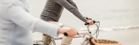 Hoger paar dat rit met hun fiets op het strand heeft