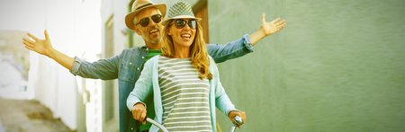 Mature couple enjoying while riding bicycle by building Stock Photo