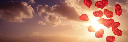 Heart balloons against cloudy sky landscape Foto de archivo