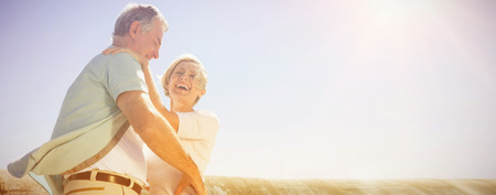 Senior woman hugging her partner on a sunny day
