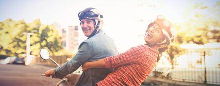 heureux couple d & # 39 ; âge mûr chevauchant un scooter dans la ville sur une journée ensoleillée