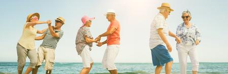 Happy senior couples dancing on shore at beach