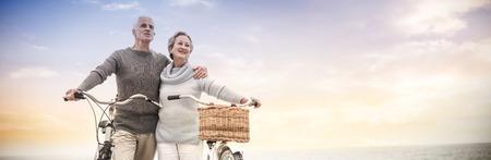 Happy senior couple with their bike on the beach Stockfoto