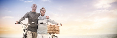 Happy senior couple with their bike on the beach Stock Photo