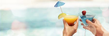 Manos de pareja tostado copa de martini cerca de la piscina