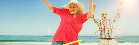 Senior couple doing hoop on beach Stock Photo