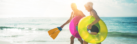 Happy senior couple walking on beach with inflatable rings and flippers during sunny day