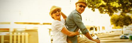 Casal maduro feliz indo para um passeio de bicicleta na cidade em um dia ensolarado Foto de archivo - 93219626
