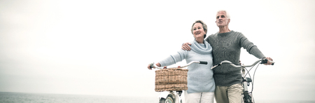 Happy senior couple with their bike on the beach Stockfoto