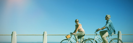 Happy casual couple going for a bike ride on the pier on a sunny day
