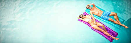 Portrait of couple relaxing in swimming pool