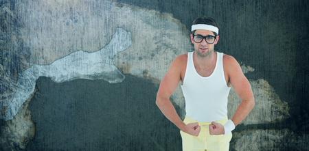 Geeky hipster posing in sportswear against rusty weathered wall