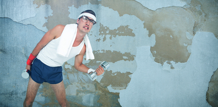 Geeky hipster lifting dumbbells in sportswear against rusty weathered wall