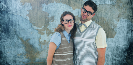 Happy geeky hipster couple with silly faces against rusty weathered wall