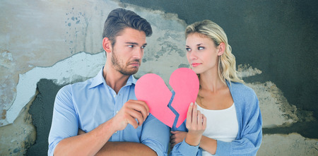 Couple holding two halves of broken heart against rusty weathered wall Stock Photo