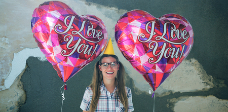 Geeky hipster holding balloons  against rusty weathered wall