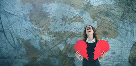 Geeky hipster holding a broken heart card against rusty weathered wall Stock Photo