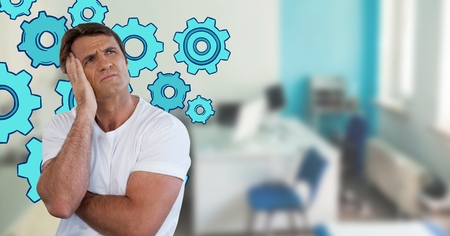 Digital composite of Confused man frowning and holding his head looking up in an office with cogs Stock Photo