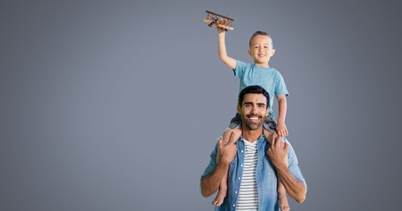 Digital composite of Father and son having fun playing with grey background
