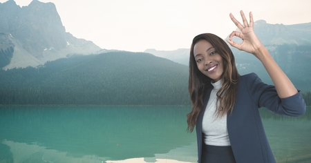 Digital composite of woman smiling with ok sign in the mountains
