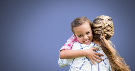 Digital composite of Mother hugging daughter with blue background