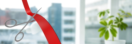 Digital composite of Scissors cutting ribbon with office windows in city Standard-Bild