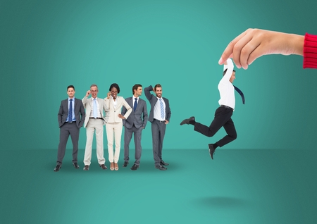 Digital composite of Hand choosing a man on a green background with business people Stock Photo